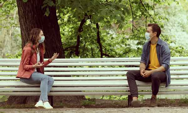 Young couple with masks on park bench could feature in kids historical fiction.